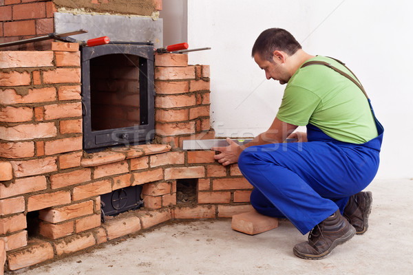 Construction worker building a masonry heater Stock photo © lightkeeper