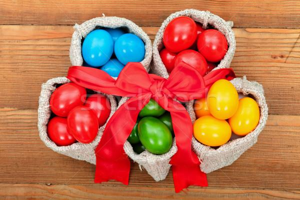 Színes húsvéti tojások kicsi zsákvászon fa asztal felső Stock fotó © lightkeeper