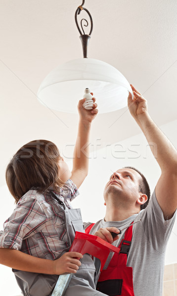 Boy helping father mounting a ceiling lamp - screwing in the lig Stock photo © lightkeeper