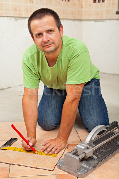 Man laying ceramic floor tiles in a new building Stock photo © lightkeeper