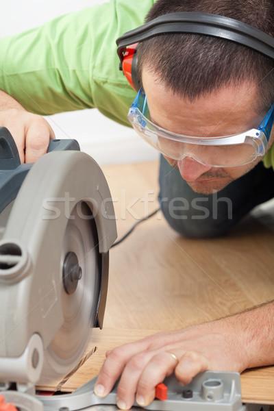 Man cutting laminate floor plank Stock photo © lightkeeper
