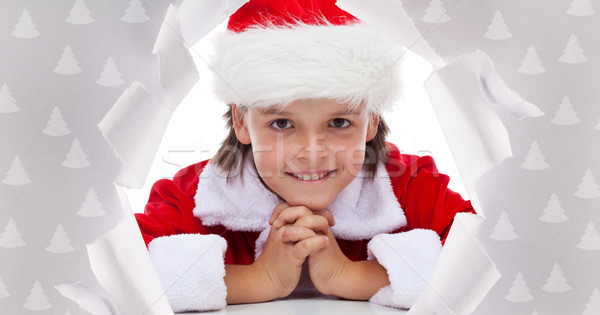 Happy christmas boy smiling through hole in wrapping paper Stock photo © lightkeeper