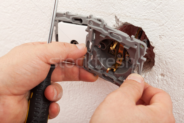Electrician hands mounting electric wall fixture Stock photo © lightkeeper