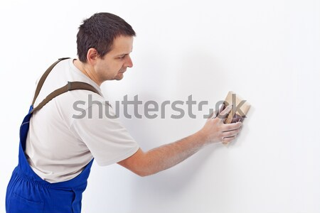 Worker scrubbing the wall with sandpaper Stock photo © lightkeeper