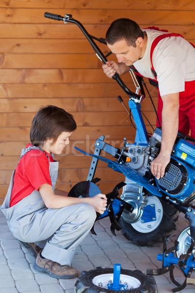 Boy helps his father mounting a cultivator machine Stock photo © lightkeeper