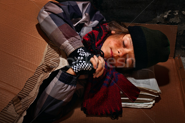 Poor beggar boy preparing to sleep on the street - covered with  Stock photo © lightkeeper