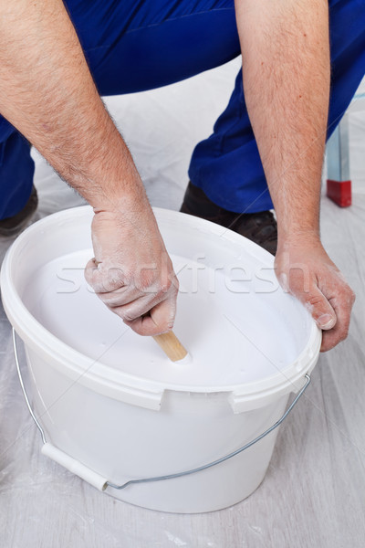 Stock photo: Worker stirring the paint - closeup on hands