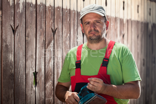 Worker with vibrating sander standing in front of old wooden fen Stock photo © lightkeeper
