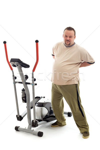 Overweight man stretching his back near a trainer device Stock photo © lightkeeper