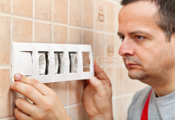 Mounting a decorative panel on electrical wall fixture Stock photo © lightkeeper