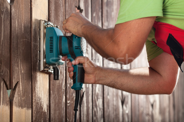 Man hands polishing old fence with power tool Stock photo © lightkeeper