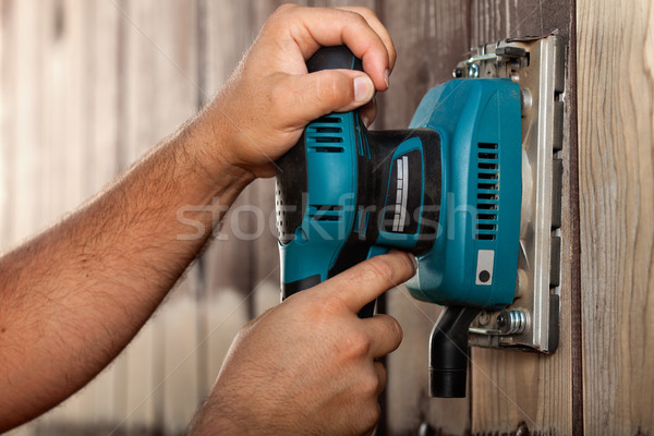 Male hands using a vibrating sander on wooden surface Stock photo © lightkeeper