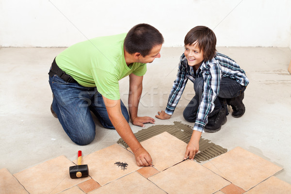 Father and son laying ceramic floor tiles Stock photo © lightkeeper