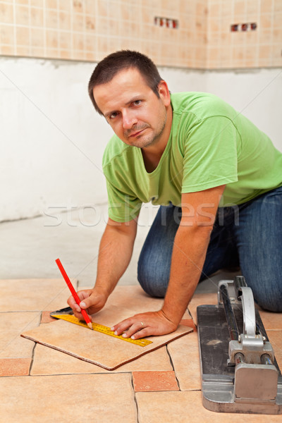 Man laying ceramic floor tiles - measuring and cutting one piece Stock photo © lightkeeper