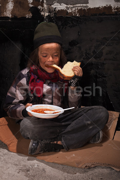 Young homeless boy eating on the street Stock photo © lightkeeper