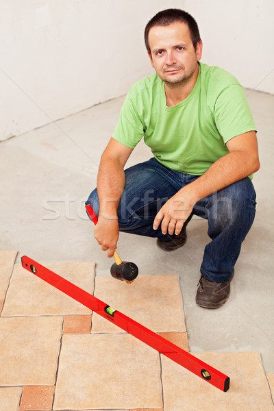 Stock photo: Worker laying ceramic floor tiles
