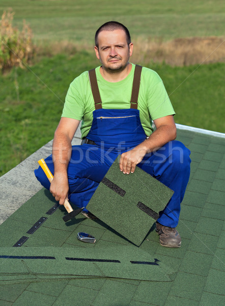 Man on the roof fastening bitumen shingles on annex building Stock photo © lightkeeper