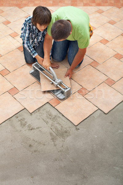 Young boy learning how to cut a ceramic floor tile Stock photo © lightkeeper