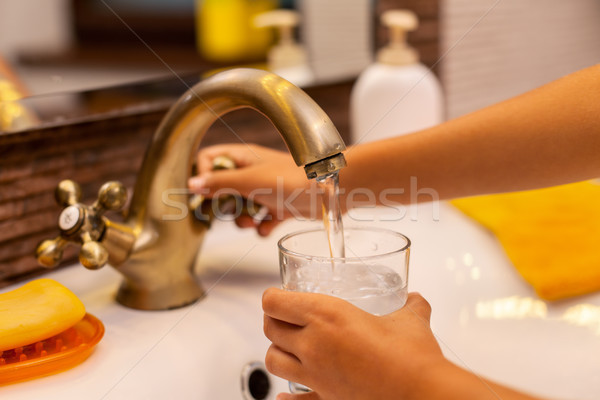 Stock photo: Child hands pouring a glass of water at the bathroom sink