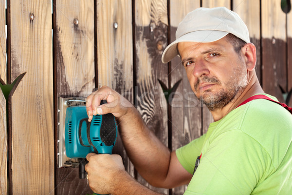 Worker polishing old wooden fence Stock photo © lightkeeper