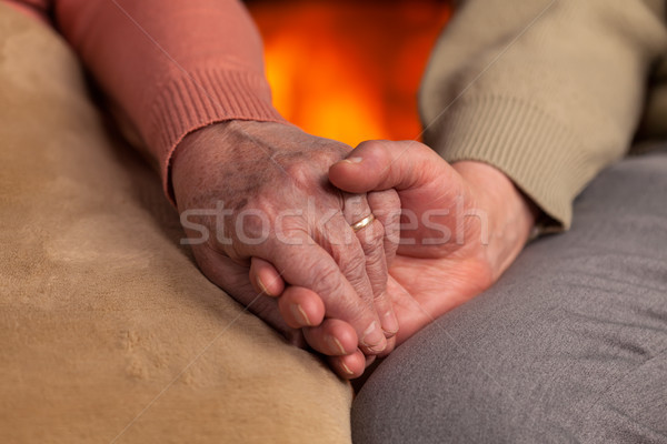 Senior old hands holding in front of fireplace Stock photo © lightkeeper