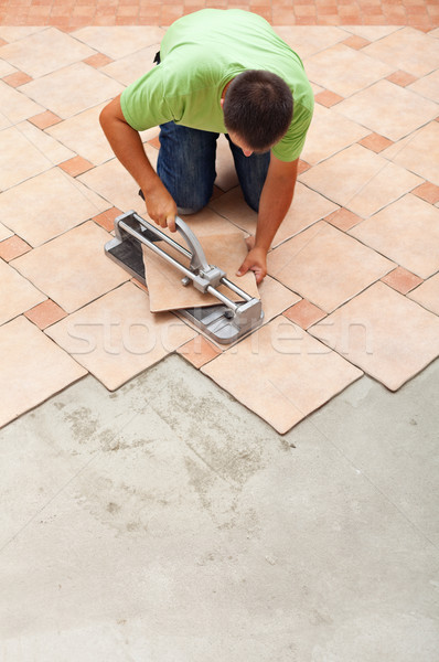 Man cutting ceramic floor tiles with manual cutter Stock photo © lightkeeper