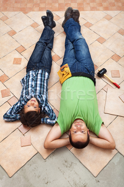 Father and son resting while laying floor tiling Stock photo © lightkeeper