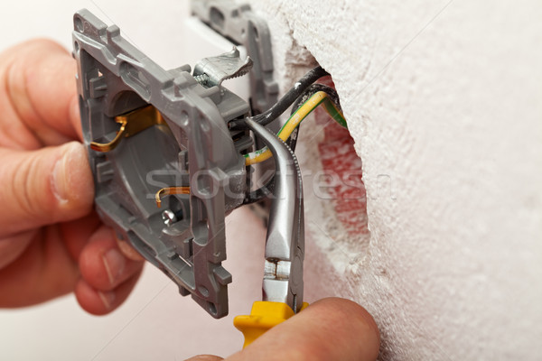 Electrician hands installing wires into electrical outlet Stock photo © lightkeeper