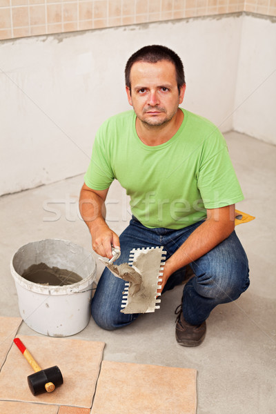 Worker laying ceramic floor tiles Stock photo © lightkeeper