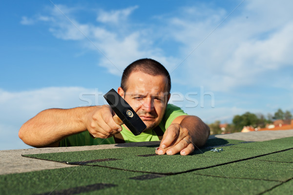 Man installing bitumen roof shingles Stock photo © lightkeeper