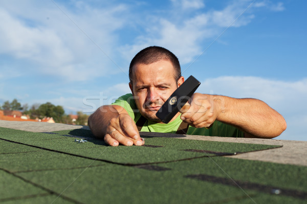 Man installing or repairing roof with bitumen shingles Stock photo © lightkeeper