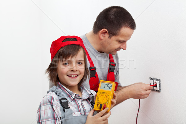 Happy boy helping his father mounting electrical wall fixtures Stock photo © lightkeeper