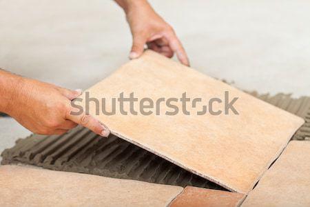 Man lays ceramic floor tiles - closeup Stock photo © lightkeeper