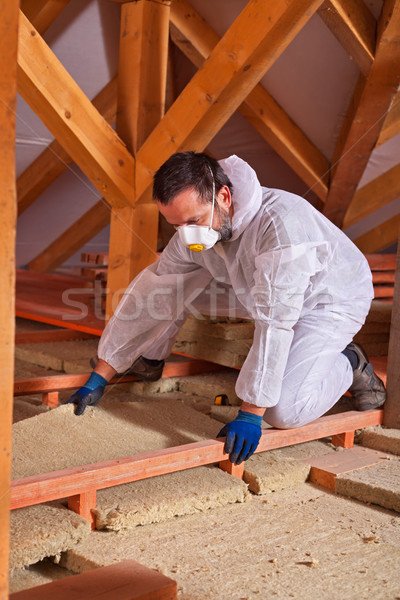 Male worker placing a rock wool thermal insulating panel between Stock photo © lightkeeper