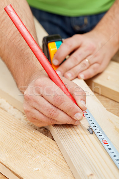 Carpenter or joiner measuring wood Stock photo © lightkeeper