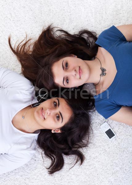 Kettő fiatal nők osztás zenelejátszó fektet padló Stock fotó © lightkeeper