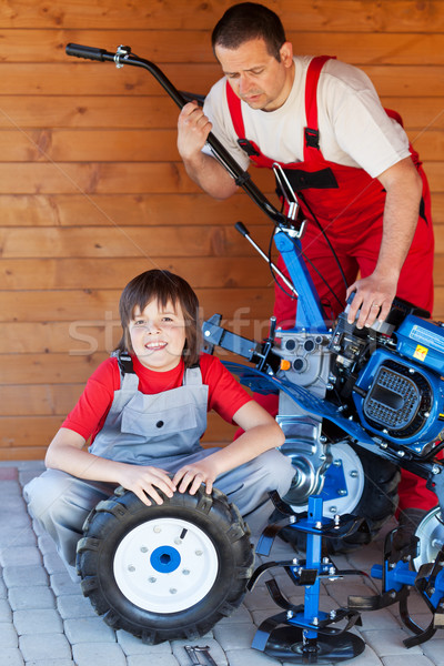 Man and boy servicing a cultivator machine Stock photo © lightkeeper