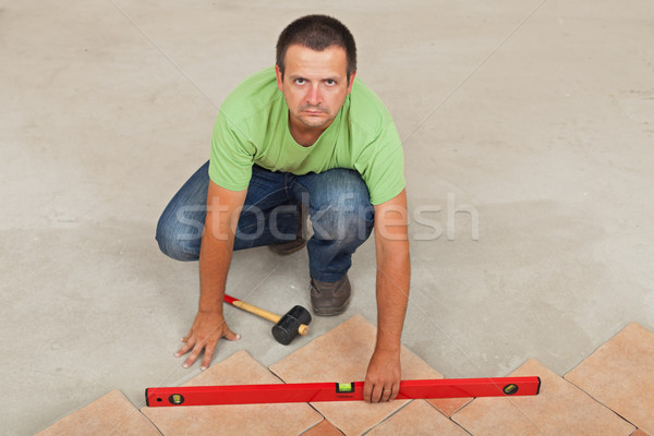 Man laying ceramic floor tiles - checking with a level, top view Stock photo © lightkeeper