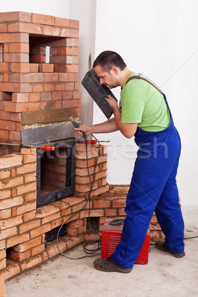 Worker installing door to a masonry heater Stock photo © lightkeeper