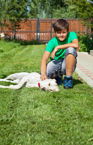 Boy petting his young labrador retriever dog Stock photo © lightkeeper
