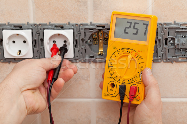 Electrician checking voltage in a partially installed electrical Stock photo © lightkeeper