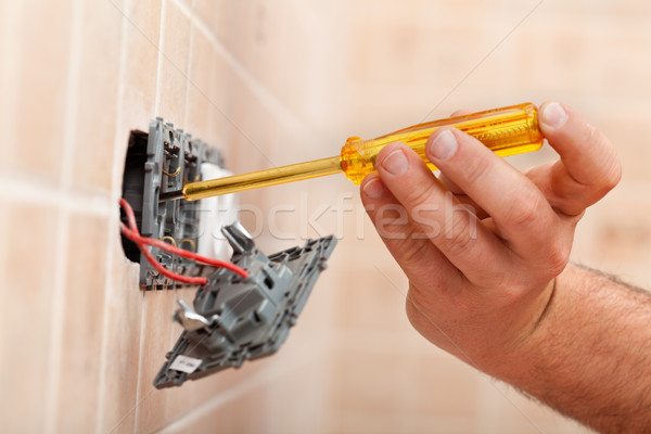 Electrician testing for electricity in electrical wall fixture Stock photo © lightkeeper