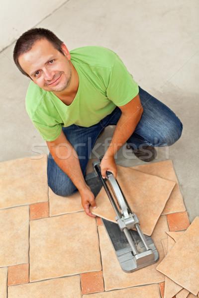 Man laying ceramic floor tiles - cutting one piece Stock photo © lightkeeper
