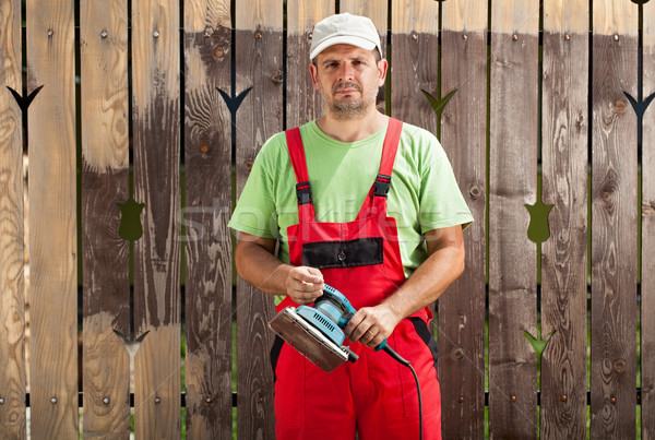 Worker man scraping old paint from fence with electric hand tool Stock photo © lightkeeper