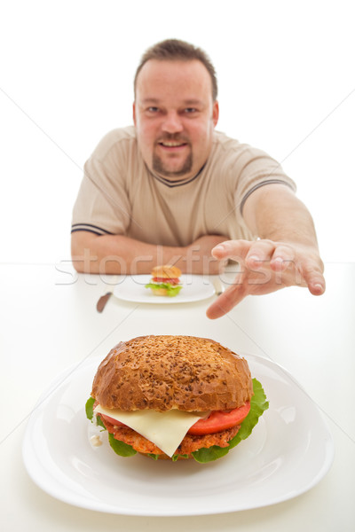 Man with small hamburger reaching for a bigger one Stock photo © lightkeeper