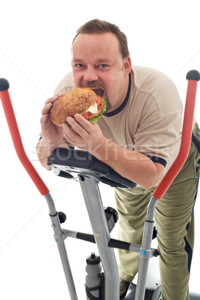 Man eating huge hamburger on a trainer device Stock photo © lightkeeper