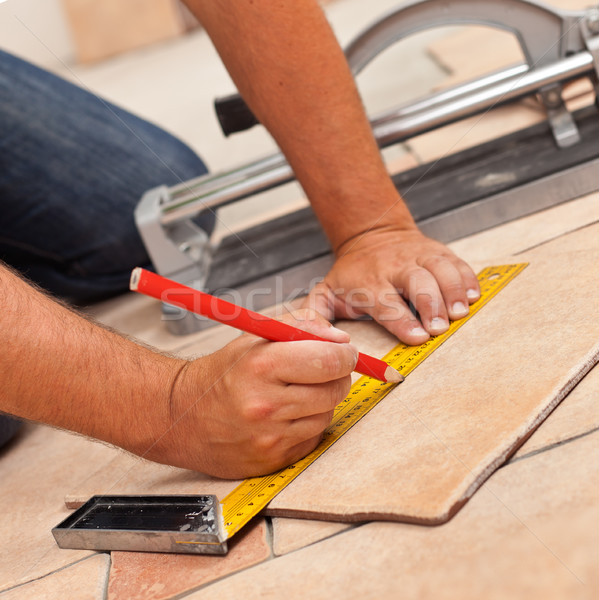 Laying ceramic floor tiles - man hands marking tile to be cut, c Stock photo © lightkeeper