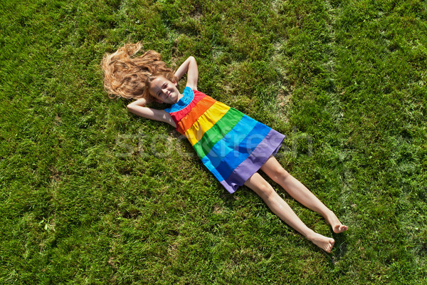 Young girl on lying on freshly mowed lawn Stock photo © lightkeeper