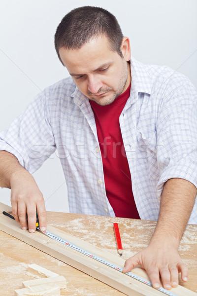 Woodwork - man measuring wooden planck Stock photo © lightkeeper