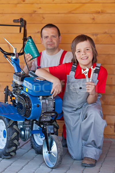 Man and young boy servicing a small tiller machine Stock photo © lightkeeper